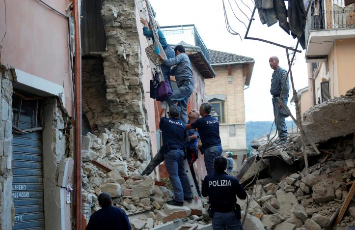 A woman is helped to leave his home by rescuers following a quake in Amatrice